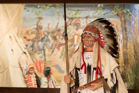 """Kostünfigur Dakota-Häuptling mit Federhaube vor dem Diorama """"Heimkehr von der Schlacht"""""""