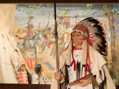 "Costumed figure of ""Dakota Chief"" in front of diorama"