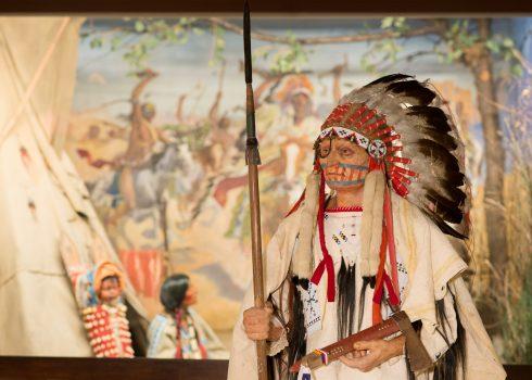 """Kostümfigur Dakota-Häuptling vor dem Diorama """"Heimkehr von der Schlacht"""""""