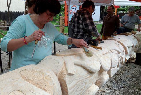 eine Frau tätigt im Vordergrund Schnitzarbeiten am Karl-May-Totempfahl