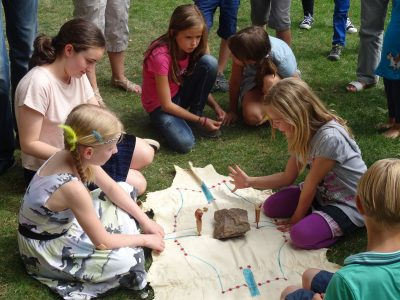 Kinder sitzen auf der Wiese und spielen ein indianisches Brettspiel