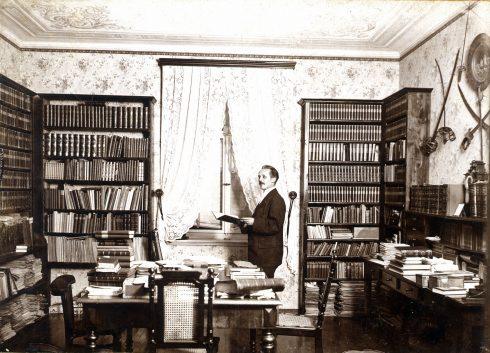 Karl May steht lesend in seiner Bibliothek, 1896
