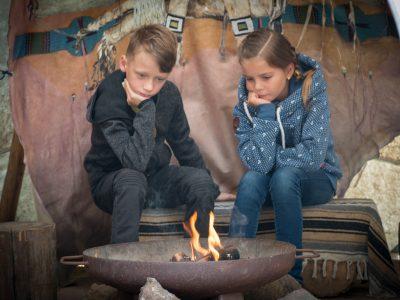 Kinder sitzen am Lagerfeuer im Tipi