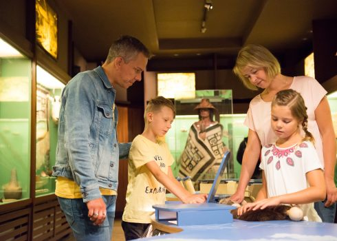 Family exploring the interactive station for kids in the log cabin Villa Bärenfett