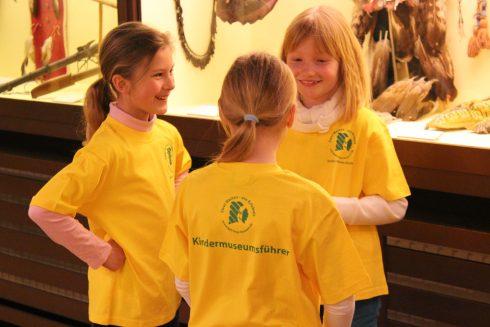 """Kindermuseumsführer in gelben T-Shirts stehen in der Ausstellung """"indianer Nordamerikas"""""""