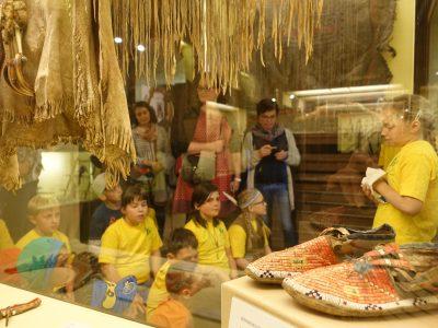 Kindermuseumsführer in gelben T-Shirts führen eine Gruppe durch die Indianer-Ausstellung