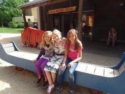 drei Mädchen sitzen vor dem Vermittlunggebäude Villa Nscho-tschi