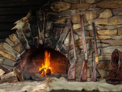 Karl Mays berühmte Gewehre vor einem Kaminfeuer: Silberbüchse, Bärentöter und Henrystutzen