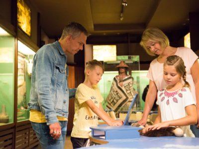 """Familie mit zwei Kindern an der Kinder-Aktiv-Station in der Ausstellung """"Indianer Nordamerikas"""""""