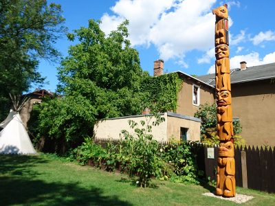 Totem pole, teepee and a raised bed in the museum park