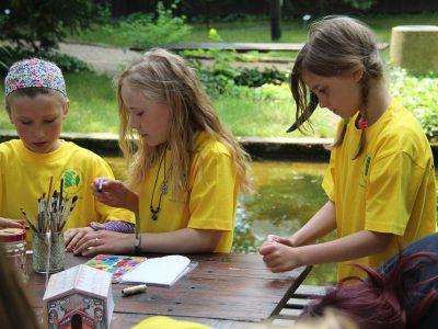 Kindermuseumsführer am Teich beim Basteln eines Langhauses