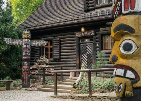 Villa Bärenfett log cabin in the summer with totem pole