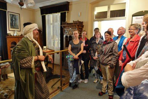 Erlebnisführung durch das Karl-May-Museum: Mann in orientalischer Kleidung führt interessierte Gäste