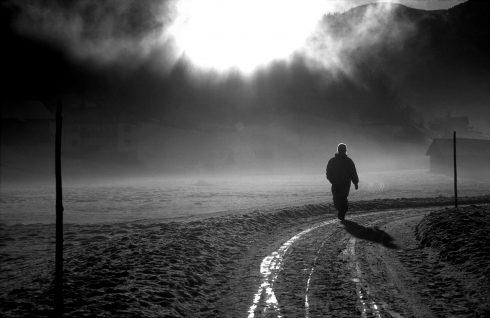 Mann geht auf einem Weg in einer düsteren Landschaft