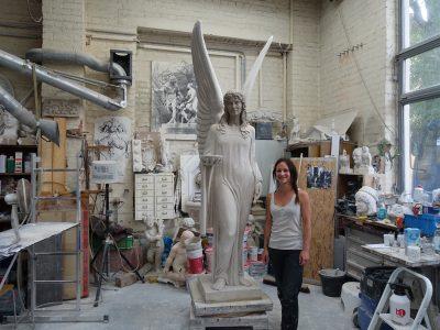 die junge Bildhauerin Romy Kumann steht vor dem Gipsmodell des Brunnenengels