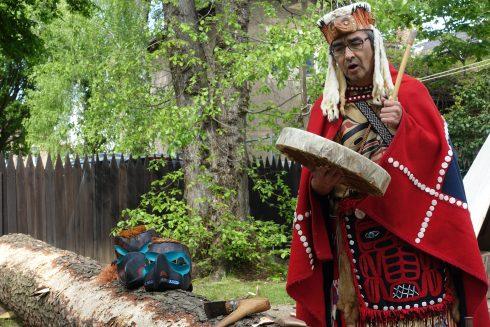 der indianische Künstler Ed E. Bryant mit roter Regalia und einer Trommel im Freien